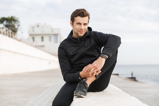 Wizerunek sprawnego dorosłego mężczyzny w wieku 30 lat w czarnej odzieży sportowej, siedzącego na promenadzie nad morzem