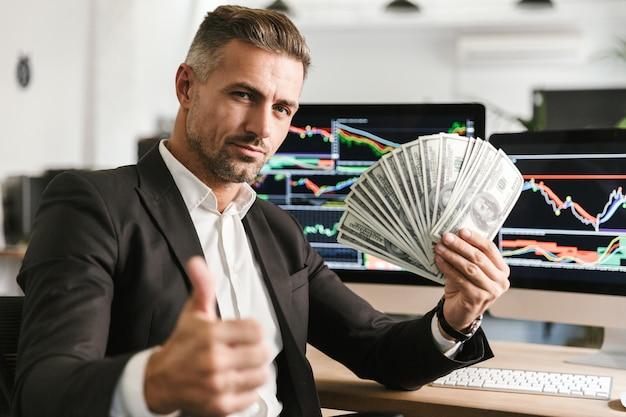 Wizerunek sukcesu biznesmen 30s na sobie garnitur, trzymając wentylator pieniędzy podczas pracy w biurze z grafiką i wykresami na komputerze
