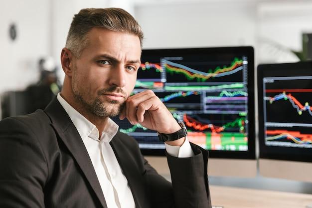 Wizerunek sukcesy biznesmen 30s ubrany w garnitur pracujący w biurze na komputerze z grafiką i wykresami na ekranie