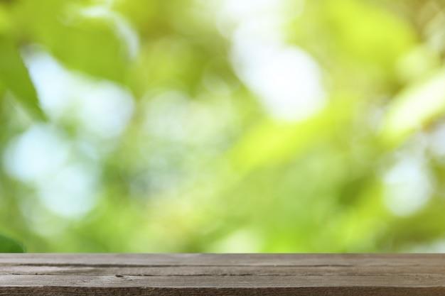 Wizerunek szary drewniany stół przed abstraktem zamazywał tło drzewa na zielonej łące