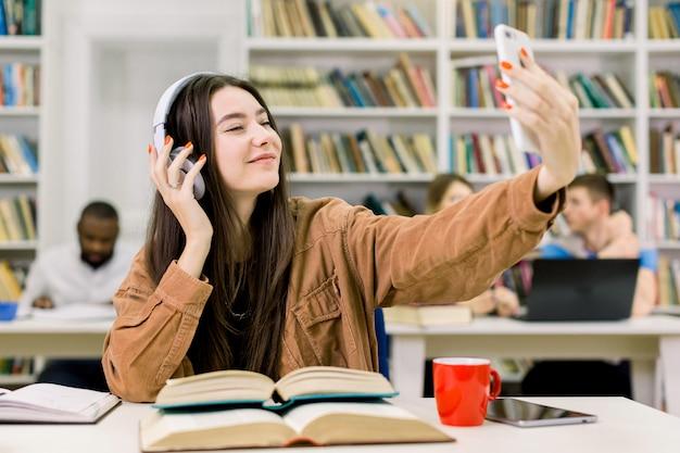 Wizerunek szczęśliwa ładna dziewczyna używa słuchawki i telefon komórkowego dla robić selfie fotografii, podczas gdy robić pracie domowej w szkoły wyższa bibliotece