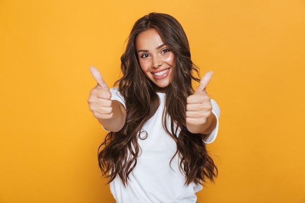 Wizerunek szczęśliwa młoda kobieta odizolowywająca nad żółtą ścianą pokazuje kciuk do góry gest.