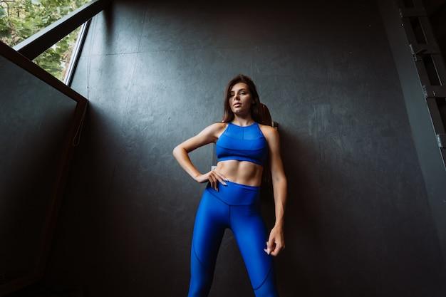 Wizerunek szczęśliwa sport młoda dziewczyna stoi i pozuje nad czerni ścianą. patrząc na kamery. kobieta odpoczynku po fitness.