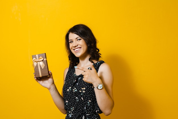 Wizerunek szczęśliwa uśmiechnięta dziewczyna otwiera prezenta pudełko i pokazuje odosobnionych gesty nad żółtą ścianą
