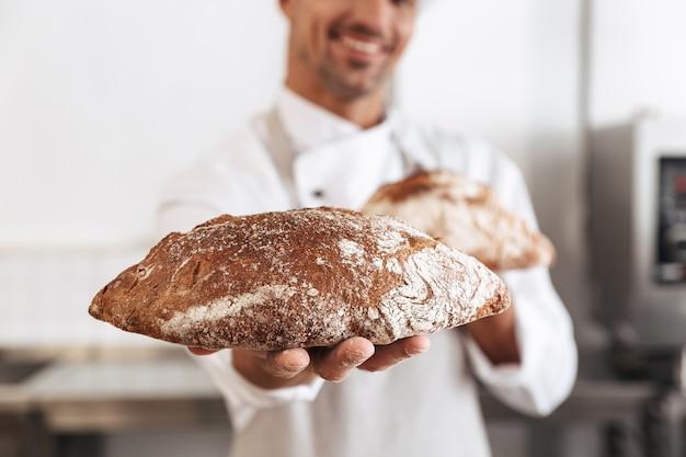 Wizerunek szczęśliwego piekarza w białym mundurze stojącego w piekarni i trzymającego chleb
