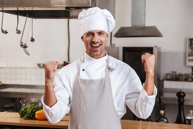Wizerunek szczęśliwego szefa mężczyzn w białym mundurze z uśmiechem, stojąc w kuchni w restauracji