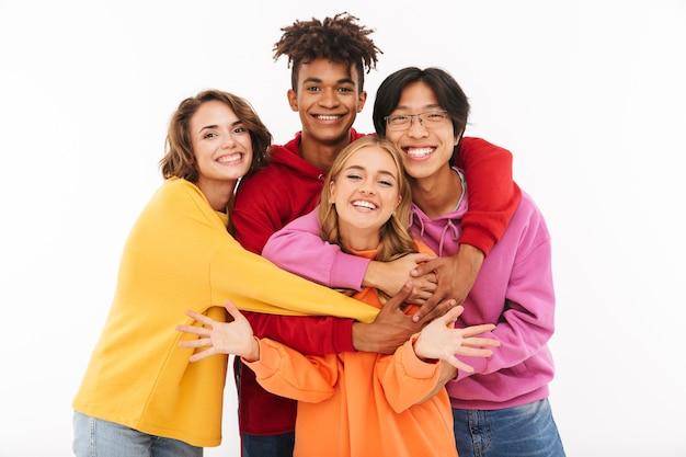 Wizerunek szczęśliwej grupy młodych studentów przyjaciół stojących na białym tle, stwarzających przytulanie.