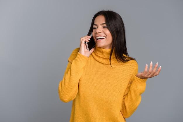 Wizerunek szczęśliwej kobiety pozowanie na białym tle nad szarą ścianą rozmawia przez telefon komórkowy.