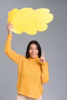 Wizerunek szczęśliwej kobiety pozowanie na białym tle nad szarą ścianą, trzymając bańkę myśli.