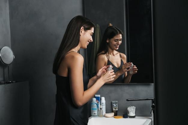 Wizerunek szczęśliwej młodej pięknej kobiety w łazience dba o jej skórę.