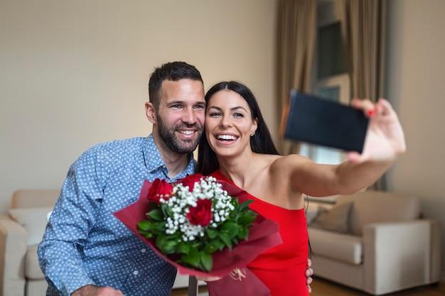Wizerunek szczęśliwej pary młodych biorąc selfie zdjęcie z kwiatami mając romantyczny czas