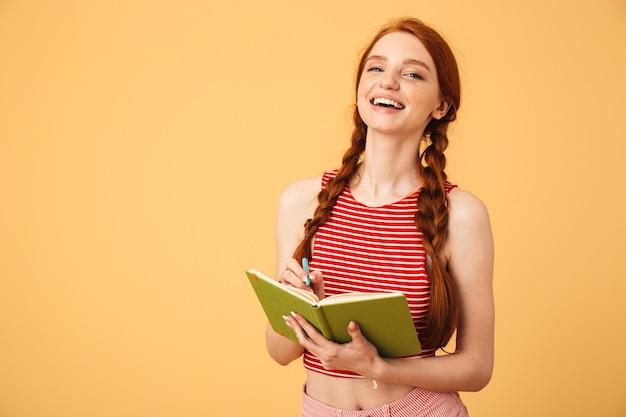 Wizerunek szczęśliwy roześmiany młoda piękna ruda kobieta pozuje na białym tle nad żółtą ścianą trzymając czytanie książki.