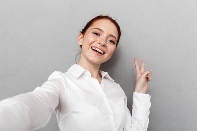 Wizerunek udanej rudowłosej bizneswoman 20s w stroju wizytowym, uśmiechający się podczas robienia selfie na białym tle nad szarym