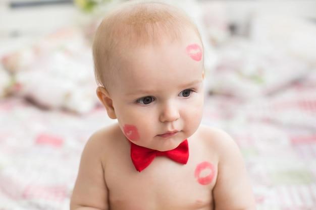 Wizerunek uroczego dziecka z czerwonymi pocałunkami na skórze, szczęśliwy chłopiec, siedzący w studiu na łóżku, anioł, romantyczne wakacje, walentynki.