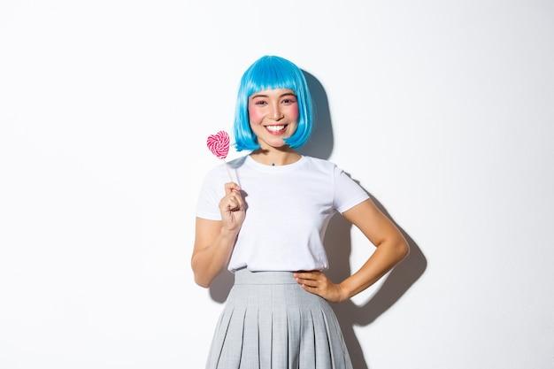 Wizerunek uroczej azjatyckiej dziewczyny w niebieskiej peruce uśmiechniętej szczęśliwie, trzymającej cukierki, przechodzącej cukierek albo psikus na halloween w jej stroju uczennicy, stojącej.