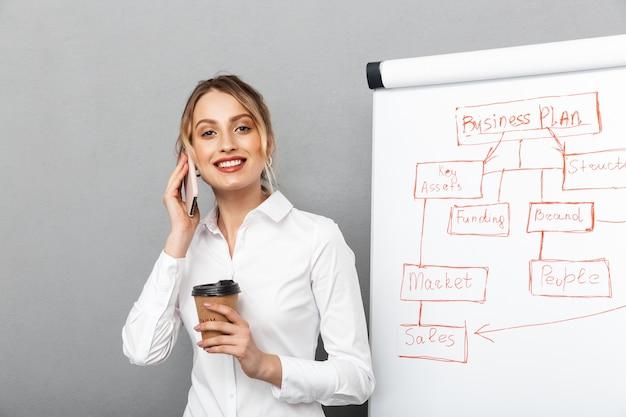 Wizerunek uroczej bizneswoman w wizytowym piciu kawy podczas prezentacji za pomocą flipchart w biurze, na białym tle