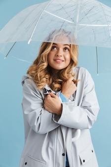 Wizerunek uroczej blond kobiety lat dwudziestych na sobie płaszcz przeciwdeszczowy stojącej pod przezroczystym parasolem