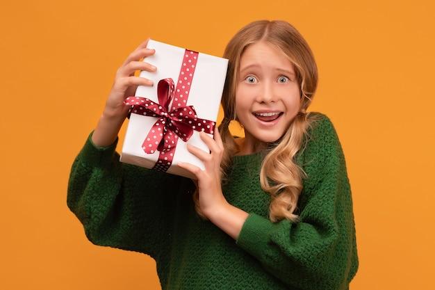 Wizerunek uroczej blondynki w wieku 12-14 lat w ciepłym zielonym swetrze, uśmiechnięta i trzymająca prezent