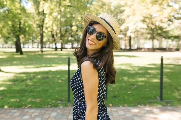 Wizerunek uroczej kobiety w stylu spaceruje po letnim parku w letnim kapeluszu, czarnych okularach przeciwsłonecznych i ślicznej sukience.