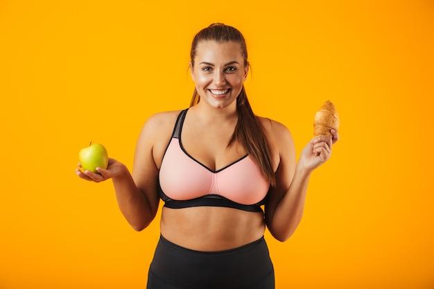 Wizerunek uśmiechnięta gruba kobieta w dresie, trzymając jabłko i rogalik w obu rękach, odizolowane na żółtym tle