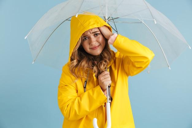 Wizerunek uśmiechnięta kobieta lat dwudziestych ubrana w żółty płaszcz stojący pod przezroczystym parasolem