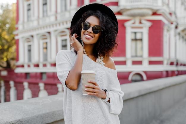 Wizerunek uśmiechnięta ładna murzynka trzyma biały kubek w białym pulowerze i czarnym kapeluszu. tło miejskie.