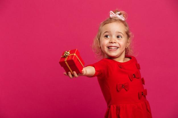 Wizerunek uśmiechnięta młoda blondynki dziewczyna w czerwieni sukni