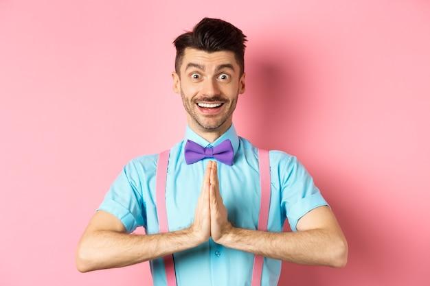 Wizerunek uśmiechniętego młodzieńca pytającego proszę, patrzącego wdzięcznie na aparat, faceta w muszce, dziękującego, stojącego na różowym tle.