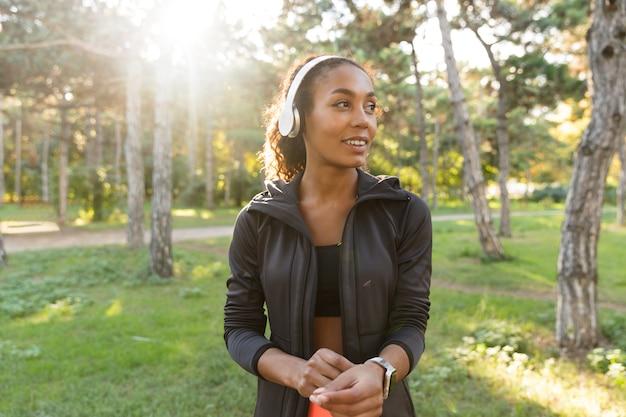 Wizerunek uśmiechniętej kobiety lat dwudziestych w czarnym dresie i słuchawkach, spacerującej po zielonym parku