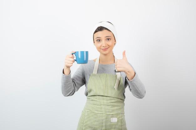 Wizerunek uśmiechniętej młodej kobiety w fartuchu z niebieską filiżanką pokazującą kciuk w górę