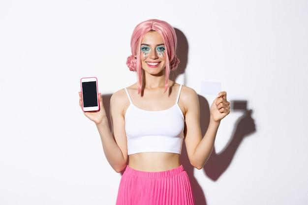 Wizerunek uśmiechniętej pięknej dziewczyny w różowej peruce z jasnym makijażem, pokazując kartę kredytową i ekran telefonu komórkowego, stojąc.