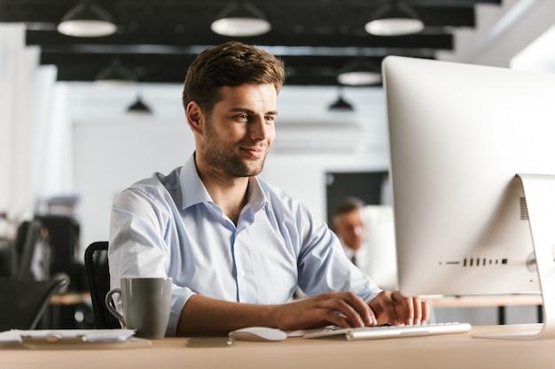 Wizerunek uśmiechnięty człowiek biznesu przy użyciu komputera, siedząc przy stole w biurze