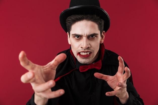 Wizerunek wampira z krwią i kłami w czarnym kostiumie na halloween atakującym