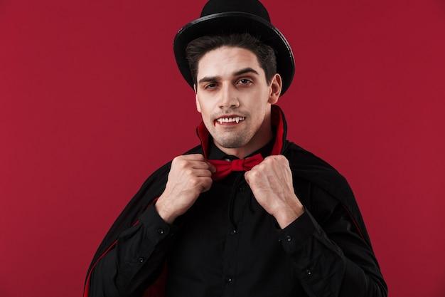 Wizerunek wampira z krwią i kłami w czarnym kostiumie na halloween, dotykającego muszki