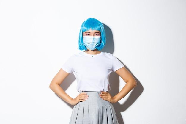 Wizerunek wesołej azjatyckiej dziewczyny gotowej na przyjęcie z okazji halloween, chroniącej się przed koronawirusem w masce medycznej