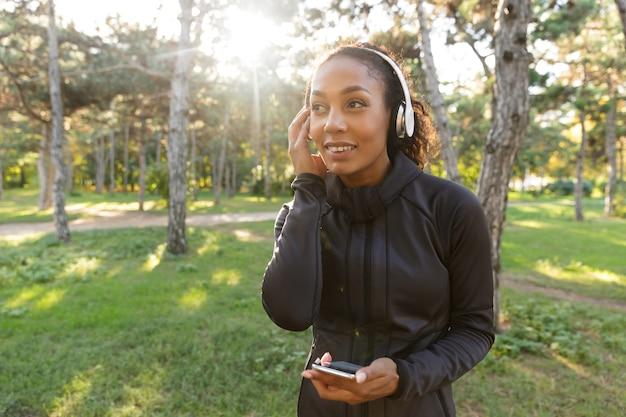 Wizerunek wesołej kobiety w wieku 20 lat w czarnym dresie i słuchawkach, korzystającej z telefonu komórkowego podczas spaceru po zielonym parku