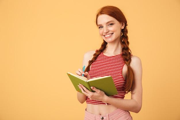 Wizerunek wesołej młodej kobiety piękne rude pozowanie na białym tle nad żółtą ścianą trzymając czytanie książki.