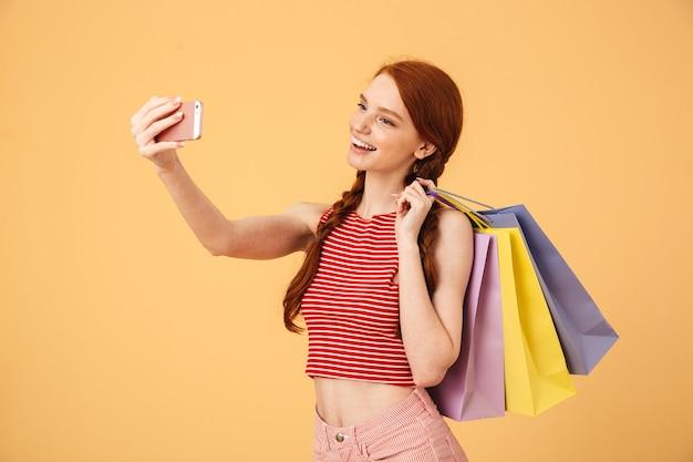 Wizerunek wesołej szczęśliwej młodej ładnej rudej kobiety pozuje na białym tle nad żółtą ścianą trzymając torby na zakupy weź selfie przez telefon komórkowy.