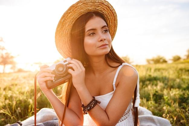 Wizerunek wiejskiej dziewczyny dwudziestki z długimi ciemnymi włosami w słomkowym kapeluszu i białej sukni trzymającej retro aparat, siedząc na trawie w parku podczas wschodu słońca