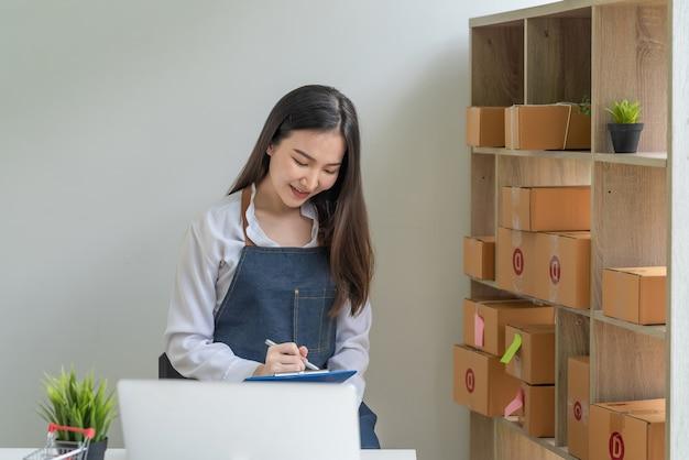 Wizerunek właściciela małej firmy, który robi notatki na temat sprzedaży online w domu.