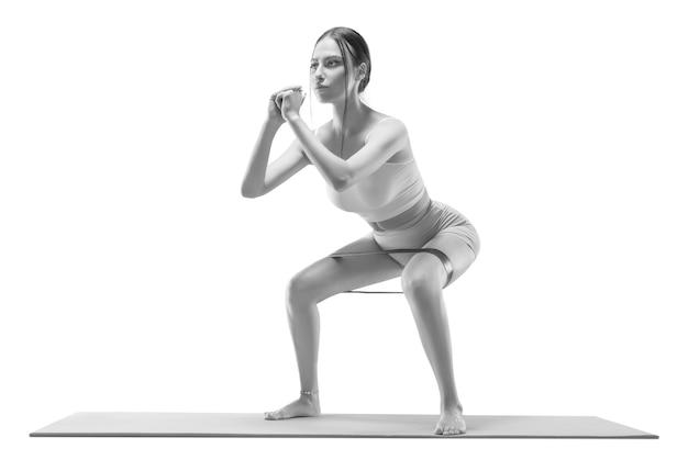 Wizerunek wysportowanej dziewczyny kucającej z gumką na macie. pojęcie kształtowania, pilates, rozciąganie. różne środki przekazu