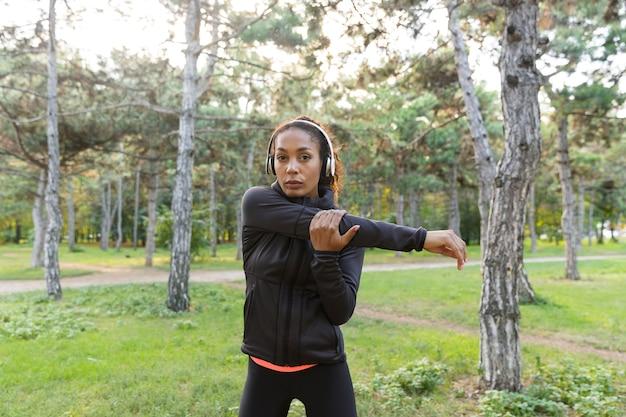 Wizerunek wysportowanej kobiety lat 20. ubrana w czarny dres, ćwicząca i rozciągająca ciało w zielonym parku