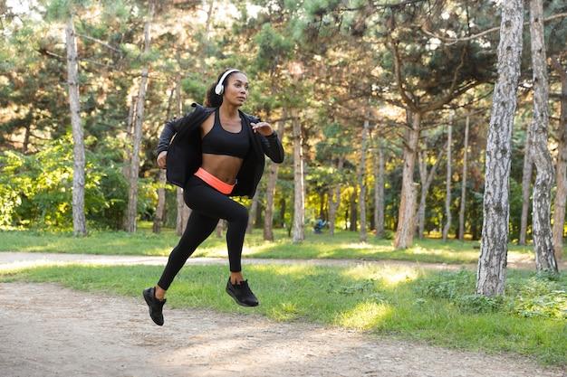 Wizerunek wysportowanej kobiety lat 20. ubrana w czarny dres i słuchawki, ćwicząca podczas biegania przez zielony park