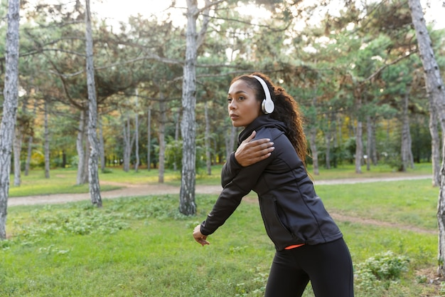 Wizerunek wysportowanej kobiety w wieku 20 lat w czarnym dresie, ćwiczącej i rozciągającej się w zielonym parku