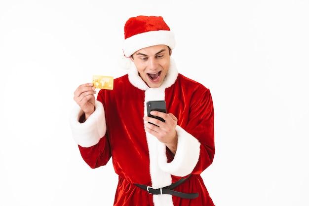 Wizerunek zachwyconego mężczyzny w wieku 30 lat w stroju świętego mikołaja trzymającego smartfon i kartę kredytową