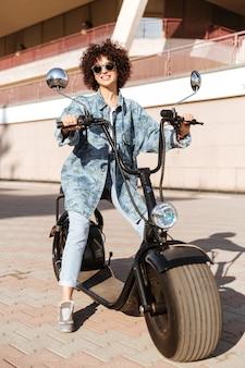 Wizerunek zadowolona kędzierzawa kobieta siedzi na nowożytnym motocyklu outdoors w okularach przeciwsłonecznych