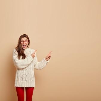 Wizerunek zadowolonej, emocjonalnej młodej kobiety z radosnym wyrazem twarzy, śmieje się z rozbawienia, wskazuje na prawy górny róg, reklamuje fajny produkt, nosi biały sweter, odizolowany na beżowej ścianie