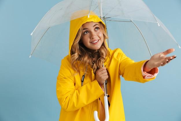 Wizerunek zadowolonej kobiety w wieku 20 lat ubrana w żółty płaszcz przeciwdeszczowy stojącej pod przezroczystym parasolem