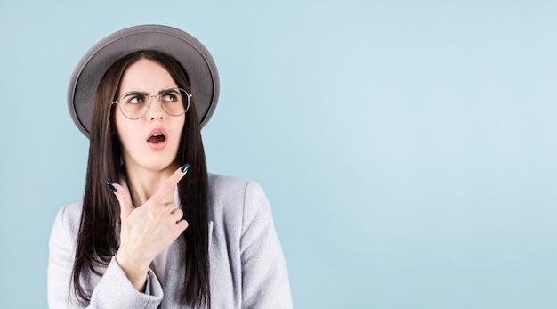 Wizerunek zaskoczony młoda kobieta z szarym kapeluszem stojącym na białym tle na niebieskim tle. patrząc na róg i wskazując.