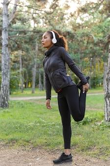 Wizerunek zdrowej kobiety po dwudziestce ubrana w czarny dres, ćwicząca i rozciągająca się w zielonym parku
